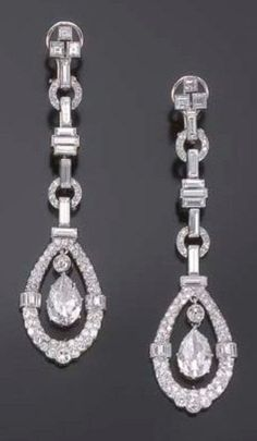 A PAIR OF ART DECO DIAMOND EAR PENDANTS, CIRCA 1930. Each consisting of a cascade of baguette and round diamond links, suspending a pendant set with a pear-shaped diamond, mounted in platinum. #ArtDeco #earrings