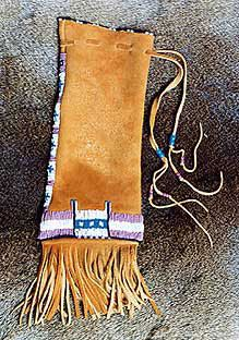 A buckskin bag designed to hold a rawhide rattle or other medicine item. They are based on Native American Paint bags and have an area of beadwork at the bottom of of the bag and beadwork strip up one side (covering the seam in the buckskin). These bags have a simple buckskin drawstring to close them. Bag width approx 12 cm. Height approx 22 cm (not including tassels). http://www.nicholaswood.net/Pages/Bags.htm