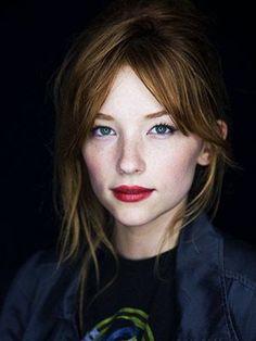 Porcelain skin, freckles, red lips.
