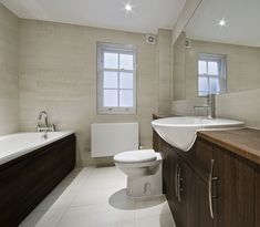 A minimalist bathroom with off-white scheme with dark wood design placed on opposite sides. The tub is white and long.