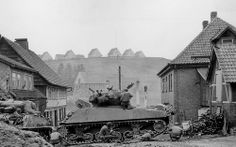 "GIs of the 1st Infantry Division ""The Big Red One"", hide the firing of a German sniper who has not yet been located, behind tanks Sherman M4A3E8 and M4A3(76)W from 745th Tank Battalion. Sankt Andreasberg, Lower Saxony, Germany. 14 April 1945."