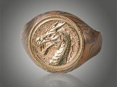 Custom designed dragon head ring that is 8mm wide at the top that tapers to 6mm in mokume of non-etched 18K yellow gold, 14K palladium white gold and 14K red gold with engraved dragon head. (engraving by Hratch Nargizian)