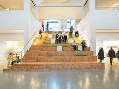 Vattenfall Arenastaden interior by Tengbom. On the ground floor of the building's atrium there is a common cafe and 'living rooms' on either side of the stairs, designed as bleachers with cushions and tables. Commercial Design, Commercial Interiors, Bleacher Seating, Tiered Seating, Lounge Seating, Workplace Design, Cool Office, Design Furniture, Atrium