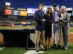 Derek Jeter #2 of the New York Yankees is presented with milestone memorabilia by members of the Steinbrenner family