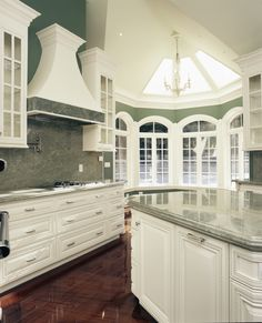 Rich dark wood flooring and expanses of green marble on countertops and backsplash complete the look.