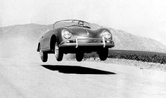 Steve McQueen jumping a porsche cabriolet on a dirt road