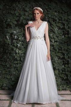 Corte clásico y romántico elaborado en crepé y tul sedoso con aplicaciones de flores en relieve en la cintura y los hombros.