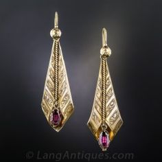 Marvelous mid-nineteenth century earrings from England with an unusual stylized leaf design, handcrafted in 15 karat gold with a lovely time-worn patina and hand-engraved detailing. Pretty plum-colored garnet drops add the finishing touch. Measure 2 inches long by 5/8 inch wide.