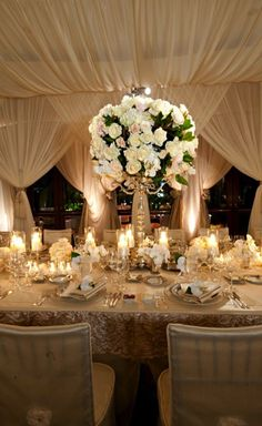 A large cream rose centerpiece and smaller arrangements along the rest of the table.