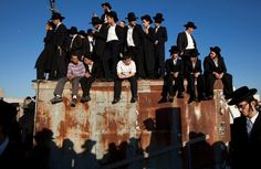 JERUSALEM : Ultra-Orthodox Jewish youths wait for the body of Rabbi Ovadia Yosef, the spiritual leader of the ultra-religious Shas political party, to be brought to a seminary before his funeral in Jerusalem on October 7, 2013.  AFP PHOTO/AHMAD GHARABLI