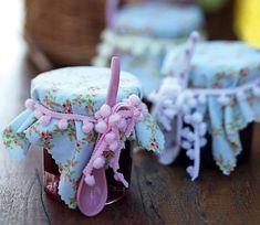 Os potes de geleia podem armazenar... geleias! Aqui, a versão caseira foi distribuída nos vidrinhos, cobertos com tecido e amarrados com fita de pompom. Uma lembrancinha charmosa para os convidados