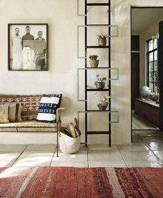 Faded red rug and geometric display shelf; House Beautiful