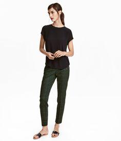 Schwarz/Gemustert. Knöchellange Slacks aus Stretchstoff. Modell mit niedrigem Bund und schmalem Bein. Schräge Ziertaschen mit Zipper und ein