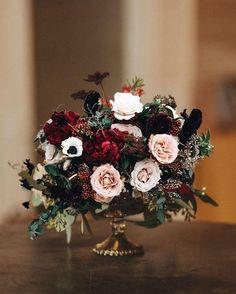 For the round tables, a goblet style bouquet surrounded by taper candlesticks!