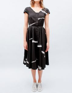 Dress with fitted waist and circle skirt bottom. V-shaped neckline with hidden snaps down center front. Darting around waist. Cap sleeves. Yoke seam detail across front. Fully lined.    Composition: 100% silk