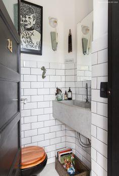 Lavabo tem bancada de concreto,  subway tiles e porta pintada de preto.