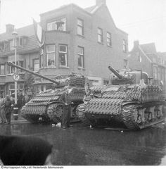 A Sherman Firefly next to a Sherman with a modified M1 105mm howitzer, in a recently liberated Den Haag, May 1945.