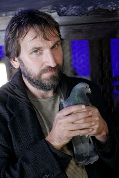 OMG Christopher Eccleston with hair, and a beard, and holding a pigeon.