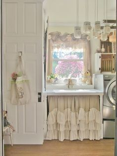 Just look at that beautiful flowering bush outside the window of this spectacular laundry room featuring sweet homemade curtains and a counter skirt made of burlap!  From Chic Cottage: Laundry Room
