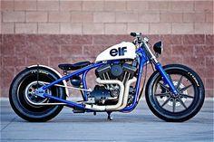 Voici le dernier bijou du studio DP Customs baptisé « Del Rey Harley Sportster » monté sur une base de 1200cc Evo.  La peinture est inspirée des formules 1 Elf des années 70.  Le Sportster Evo de 1995 a subi de nombreuses modifications avec un échappement fait main, de nouveaux freins Brembo et des pneumatiques Night Dragon de chez Pirelli.  Une vraie merveille pour les amateurs du genre.