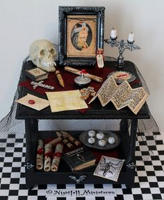 A Gothic Black Wooden Vampire Hunters Table decorated with Bat Motifs, a red satin cloth and black fine netting.  Includes a vampire skull,
