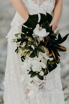 bride holding tropical wedding bouquet with greenery and white orchards Tropical Wedding Centerpieces, Tropical Wedding Bouquets, Tropical Flower Arrangements, Palm Wedding, Floral Wedding, Wedding Flowers, Hand Bouquet Wedding, Tropical Weddings, Wedding Dress