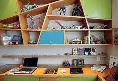 Para organizar o quarto de estudos e brinquedos dividido por dois irmãos, a arquiteta Maria Amélia Raeder projetou uma moderna estante, que fica sobre a bancada. Com desenho instigante, os nichos geométricos têm portas laqueadas de azul e verde