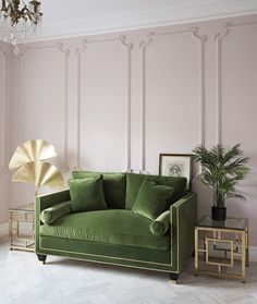 Pale pink walls and olive green sofa in an art deco interior style