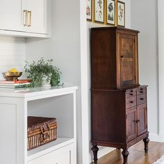Adding vintage wood pieces to a new kitchen immediately infuses personality and patina into a crisp, clean space. This vintage dental cabinet becomes a cool home bar in this classic shaker kitchen renovation. Vintage audobon prints frame the piece. Design by: Trim Design Co. Photography by: Joyelle West  #trimdesignco #classicshakerkitchen #vintagefurniture #vintagekitchen