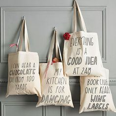 "Joy tote bags: ""I can hear a chocolate foil from 100 yards"", ""My kitchen is for dancing"", ""Everything is a good idea at 2 a.m."", ""My book club only reads wine labels""."