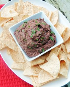 Bean dip in a square while bowl on a white platter with tortilla chips. Red towel and wooden background.