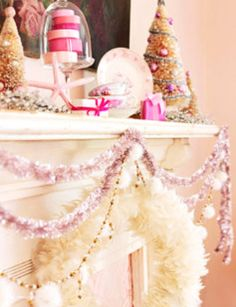 Christmas mantel with pink and white tinsel and mini trees. #holiday #inspiration