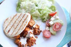 Een heerlijk en snel recept: pita broodje met hete kip, zelfgemaakte knoflooksaus en een frisse Griekse salade.