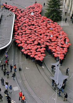 Umbrellas, Paradenplatz, Zürich, Switzerland - Members of Swiss trade union Unia hold red umbrellas while forming a large fish apparently swimming after a smaller shark in Zurich. The action was reportedly part of a protest against financial sharks. Protest Kunst, Protest Art, Umbrella Art, Under My Umbrella, Umbrella Street, Art Public, Parasols, Pictures Of The Week, Random Pictures