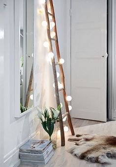 Lean an antique ladder against the wall and cover it with string lights for some unusual atmospheric lighting.