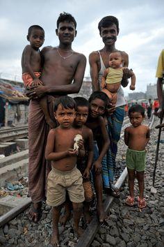 https://flic.kr/p/dQwLVD   Bangladesh   Men with their children on the side of railroad tracks. Dhaka, Bangladesh.