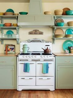 Maple counters with breadboard ends flank a 1950s-era O'Keefe & Merritt six-burner range. Custom cabinets and vent hood are painted in Benjamin Moore's Prescott Green. | Photo:  Mark Lohman | thisoldhouse.com