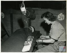 Army nurse adjusts an IV in a soldier's arm in Italy, circa 1944-1945. U.S. Army Signal Corps, Gift in Memory of William F. Caddell, Sr., from The Digital Collections of the National WWII Museum, 2007.048.112.
