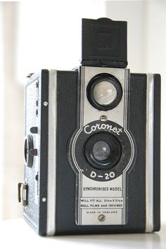 """The Coronet D20 Box was introduced in 1937. It is similar to the model B20 except for the following: Big, flip-up viewfinders; Square format (12 images sized 6"""" x 6""""); Stamped geometric decorations; strap lugs on the top of the camera. Two aperture choices (f16 and f22) with a fixed shutter speed, plus bulb mode. Both aperture and shutter speed are controlled by pull-out switches above the shutter release lever.  Accepts both 120 and 620 rollfilm. Made in England."""
