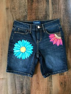 Painted Denim Old Navy denim shorts with hand painted Blue and Pink Daisies. New Size 10 Regular Care Instructions: Machine wash and dry inside out. Unique, one of a kind, hand painted item. Painted Jeans, Painted Clothes, Hand Painted, Long Jean Shorts, Short Jeans, Diy Clothes Jeans, Kids Clothing Brands List, Clothing Items, Lace Shorts