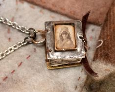 Tiny bound book necklace. A small vintage Victorian etching rests under a resin-filled bezel on the front cover.