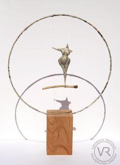 """Sculpture de femme en papier journal, montée sur un """"trapèze"""" en bois flotté, maintenu par des fils nylon sur un cercle de métal recouvert de papier journal. Le tout sur socle de bois de noyer. Sculpture mobile, la femme peut se balancer. Par Vanessa RENOUX, 2015."""