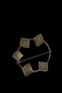 Annular brooch; silver; oval wire hoop alternately flat and twisted having five gilt lozenge-shaped plates applied, decorated with chased quatrefoils inside double tooled borders.