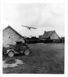 A piper cub plane swoope in for a landing on a field at Saint George d'Elle … to inspect the terrain which cover on their way to hill 192 = [Un avion d'observation Piper Cub va atterrir dans un champ (au premier plan, deux soldats dans une jeep) ].