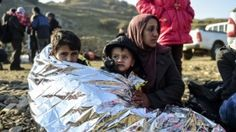 A Syrian family waits after arriving on the Greek island of Lesbos along with other migrants and refugees, on November 17, 2015.