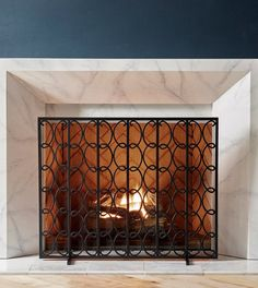 A stylish looping pattern characterizes this contemporary iron fireplace screen. Features wire mesh to protect your space from sparks and embers.