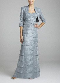 Sparkle and shine on any dance floor in this fabulous lace jacket dress!  Sleeveless bodice features figure flattering empire waist.  Exquisitelace shimmer fabric is eye-catching and stunning.  Multi tiered skirt adds drama and dimension.  3/4 sleeve jacket adds just the right amount of coverage.  Fully lined. Back zip. Imported polyester. Dry clean.