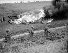 Troops file past the burning wreckage of a German Dornier bomber, shot down while bombing a Belgian town, 14 May 1940.