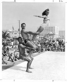 """Vintage photo Sept. 6, 1954  Santa Monica's Muscle Beach crowds were treated to the show they have come to expect Labor Day weekend. DeForrest Most, 37, is bottommost in this typical pyramid pose that also includes Art Kidder, 37, and Sandra Hollabaugh, 14.  (via the book """"Imagining Los Angeles: Photographs of a 20th Century City,"""" published by The LA Times in 2000. Credit: Bill Beebe / Los Angeles Times)"""