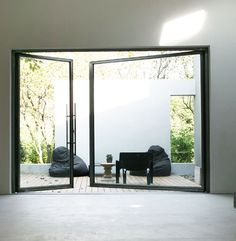 BLACK backyard design lifesize floor-to-ceiling windows - black lounge couch & chair  -  Modern Minimalistic Home Exteriors & Interiors- HOME INTERIOR DESIGN IDEAS FOR YOUR MODERN MINIMALIST CHIC SELF - HOLLYWOOD HILLS LIFESTYLES - EXPENSIVE TASTE  - Karina Porushkevich #karinarussianpowpow {http://www.karinaporushkevich.com}